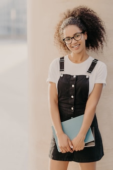 Cheerful young afro student carries notepads or diary, wears white t shirt, black sarafan