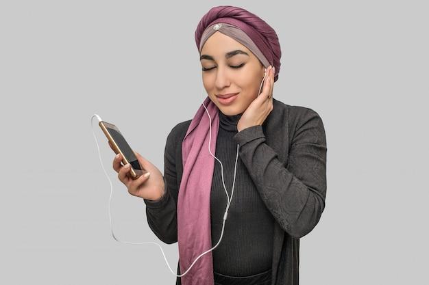 陽気な若いアラビアの女性は電話を保持します。彼女はヘッドフォンで音楽を聴きます。モデルは目を閉じたままにします。