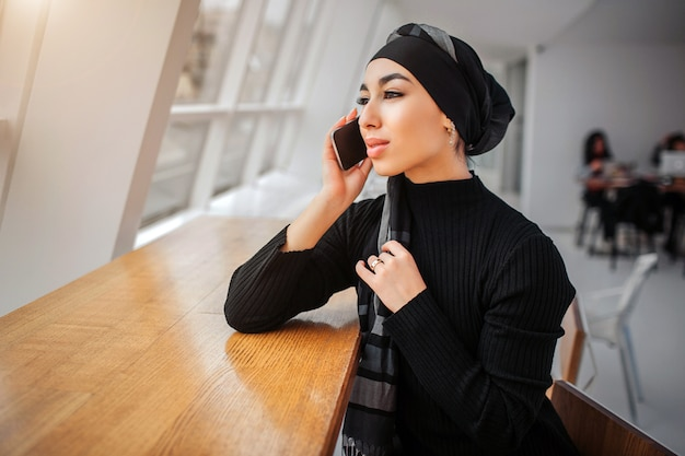 쾌활 한 젊은 아라비아 여자 키가 큰 테이블에 앉아서 창을 봐. 그녀는 전화로 이야기합니다. 모엘이 히잡의 가장자리를 만집니다.