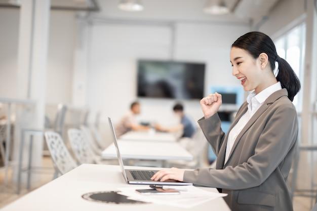 노트북을 사용하는 쾌활한 젊은 아시아 비즈니스 여성