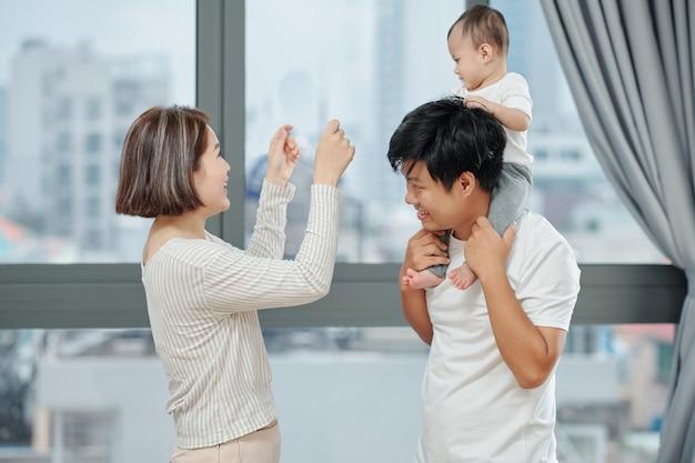 집에서 신생아와 놀고 즐기는 쾌활한 젊은 아시아 부부