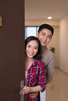 Cheerful young asian couple inviting people to enter in home