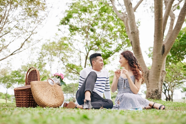 Cheerful young asian couple in love resting on blanket in park and talking