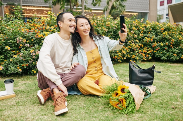 Cheerful young asian couple sitting on loan in city park and taking selfie for social media when enjoying romantic date