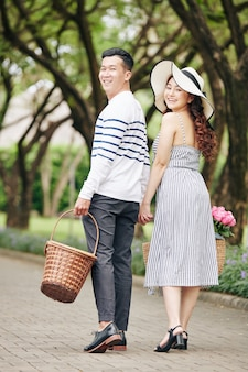 Cheerful young asian couple walking in city park, turning back and looking at camera