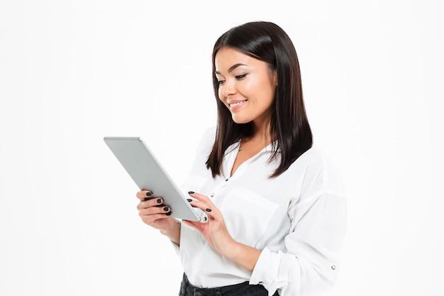 Cheerful young asian lady chatting by tablet computer