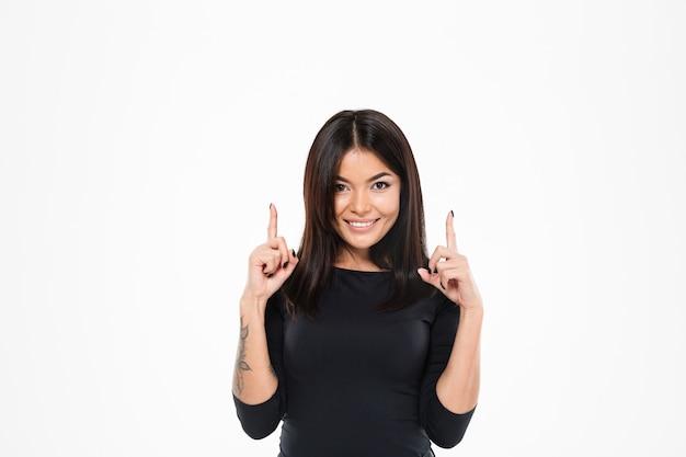 Giovane signora asiatica allegra che indica il copyspace.