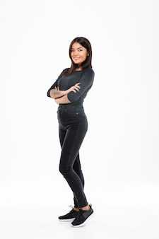 Cheerful young asian lady standing isolated