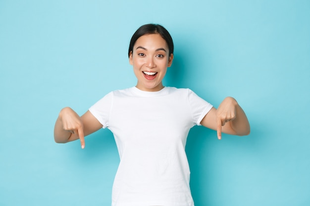 Cheerful young asian lady in white t-shirt pointing fingers down and smiling excited, looking upbeat while demontrating banner, offer special discount promo, standing blue background.