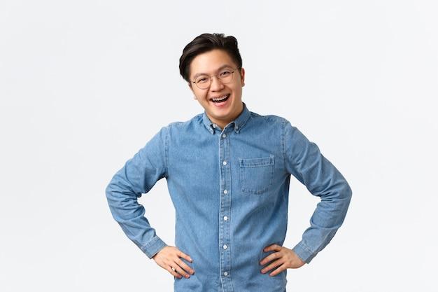 陽気な若いアジア人男性従業員、話し合いをしている同僚、幸せそうに笑って、話している間熱狂的に見えます。白い壁の上に満足して立っている中かっこと眼鏡を持つ男。
