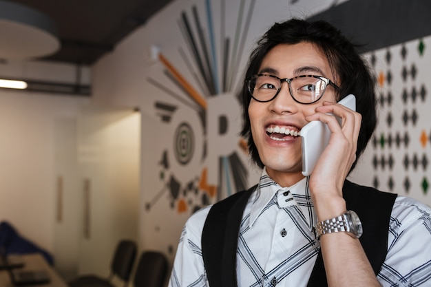 Cheerful young asian man talking by mobile phone