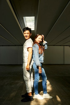 Cheerful young asian man and woman standing back to back and smiling at camera