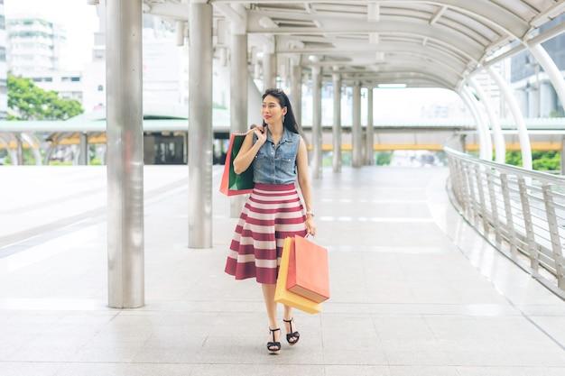 쇼핑을 하고 종이 쇼핑백을 들고 행복한 젊은 아시아 여성