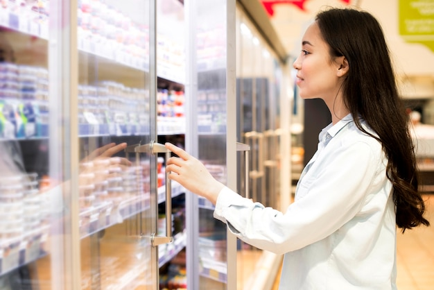 Cheerful young asian woman choosing dairy products at supermarket