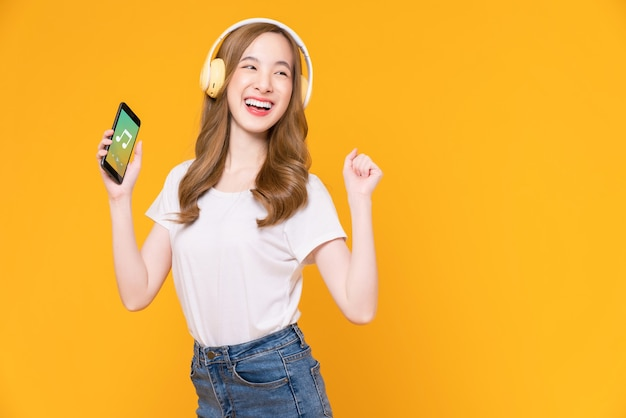 Cheerful young asian woman in headphones listening to music and enjoy favourite playlist application on smartphone with dancing on orange background.