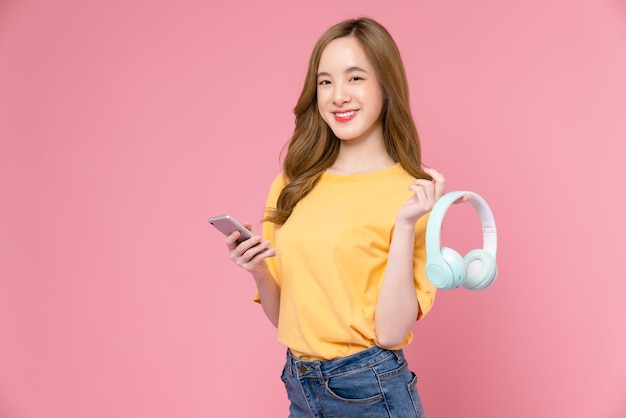 Cheerful young asian woman holding headphones listening to music and enjoy favourite playlist application on smartphone with dancing on pink background.
