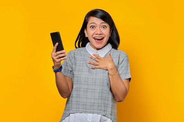 휴대폰을 들고 노란색 배경 위에 손바닥을 얹은 쾌활한 젊은 아시아 여성
