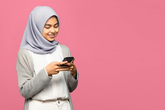 휴대 전화를 들고 화면에보고 웃 고 쾌활 한 젊은 아시아 여자