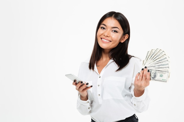 Cheerful young asian woman holding money using mobile phone.