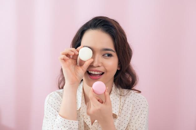 ピンクの壁の上の目の前に2つのマカロンを保持している陽気な若いアジアの女性。