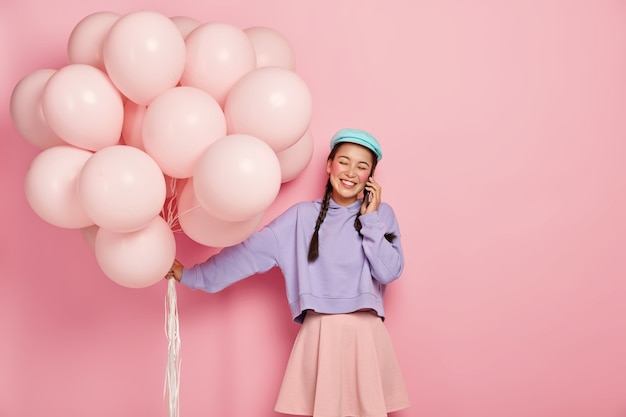 陽気な若いアジアの女性は、気球を持って、スマートフォンを介して友人に電話をかけ、ファッショナブルな服を着て、親しい人々からお祝いを受け取る喜びを得ます。