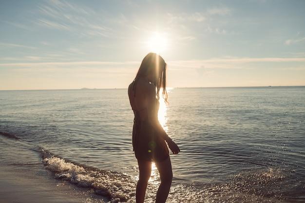 夏休みの熱帯の海のビーチで輝く茶色のドレスを着た陽気な若いアジアの女性