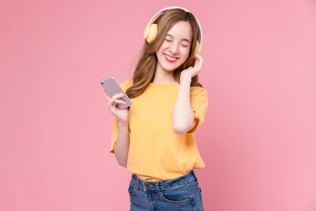 헤드폰을 끼고 음악을 듣고 분홍색 배경에서 춤을 추며 스마트폰에서 좋아하는 재생 목록 응용 프로그램을 즐깁니다.