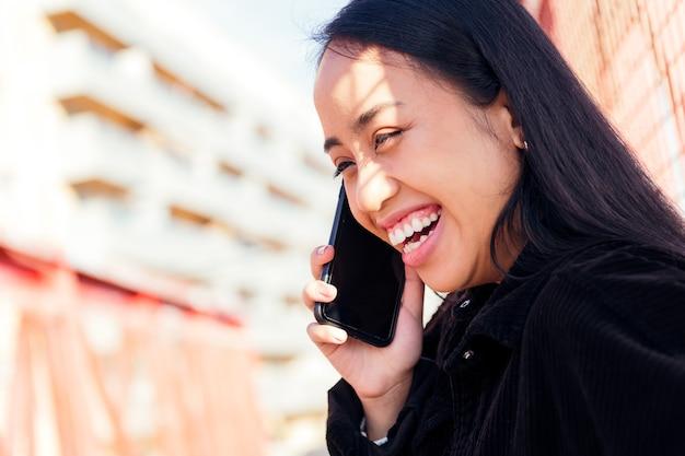 야외에서 전화 통화를 하면서 웃고 있는 쾌활한 젊은 아시아 여성