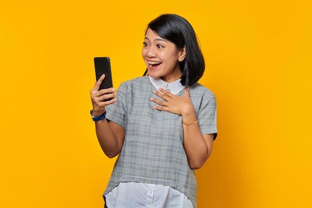 쾌활한 젊은 아시아 여성 휴대 전화를보고 노란색 배경 위에 가슴에 손바닥을 유지