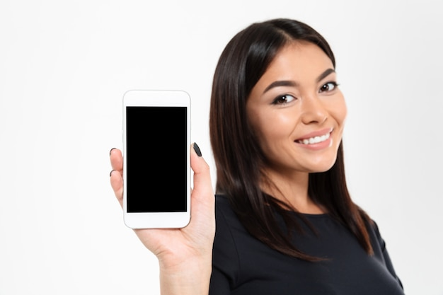 Cheerful young asian woman showing display of mobile phone