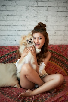 Cheerful young asian woman sitting on couch at home and holding small dog