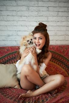 自宅でソファに座って、小さな犬を保持している陽気な若いアジア女性