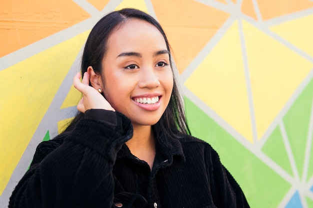 화려한 벽에 기대어 웃고 있는 쾌활한 젊은 아시아 여성