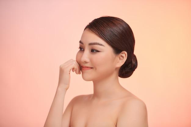 白で隔離の顔に触れる陽気な若いアジアの女性