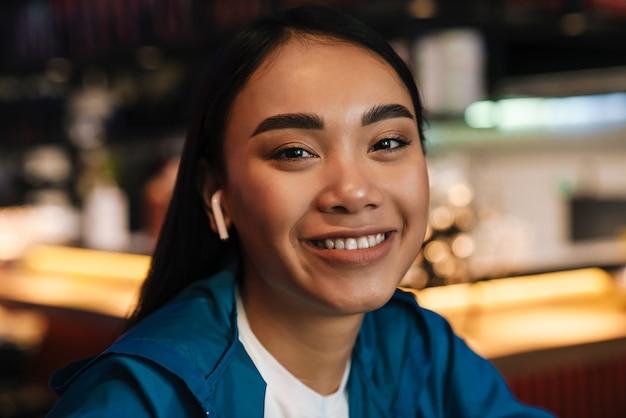 Веселая молодая азиатская женщина, использующая беспроводные наушники и улыбаясь, сидя в кафе