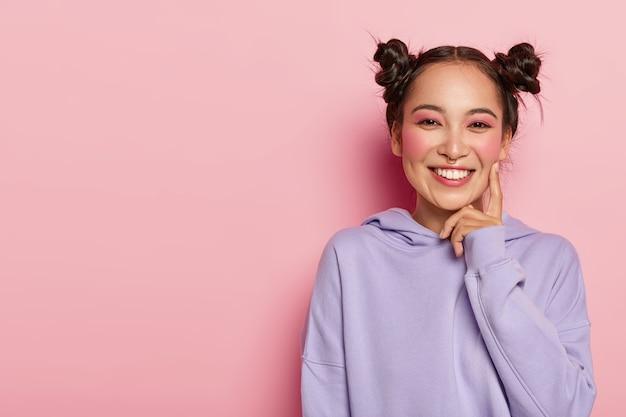 부드러운 미소로 쾌활한 젊은 아시아 여성, 캐주얼 스웨트 셔츠를 입고 자연스러운 외모를 가지고 있으며 뺨에 검지 손가락을 유지하고 행복하게 미소 짓습니다.
