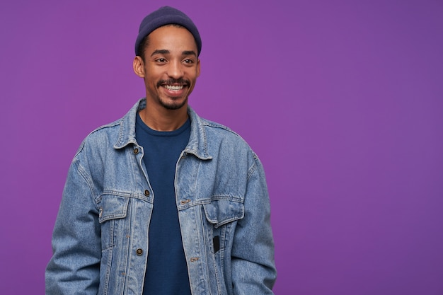 Cheerful young attractive bearded brunette man with dark skin looking positively aside with charming smile, wearing blue cap, pullover and jeans coat while posing over purple wall
