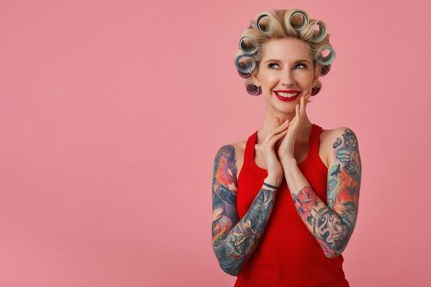 문신을 한 손으로 쾌활한 젊은 매력적인 금발 아가씨 웃고 꿈꾸는 위쪽으로 찾고, 곧 파티를 예고하고 준비하고, 분홍색 배경에 서서