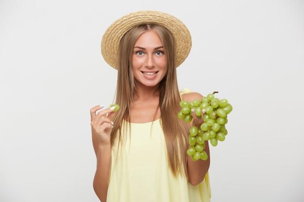 白い背景の上にポーズをとっている間黄色のシャツを着て、幸せそうに笑っている間彼女の白い完璧な歯を示すカジュアルな髪型の陽気な若い魅力的なブロンドの女性