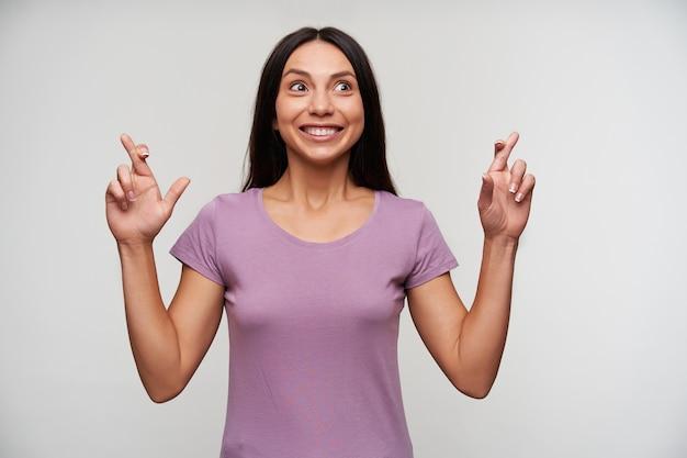 Веселая молодая привлекательная кареглазая дама в фиолетовой футболке счастливо смотрит в сторону с широкой улыбкой и поднимает руки со скрещенными пальцами, стоя