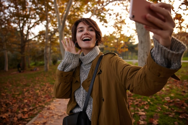 Cheerful young attractive brown haired female dressed in warm cosy wear keeping her hand raised while taking selfie on her smarthope, standing over blurred park