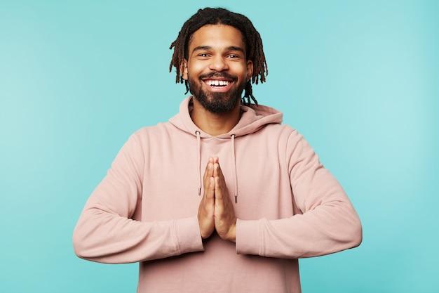 Allegro giovane attraente dai capelli castani ragazzo con la barba che sorride ampiamente alla macchina fotografica e piegando i palmi sollevati insieme, vestito con una felpa con cappuccio rosa mentre posa su sfondo blu