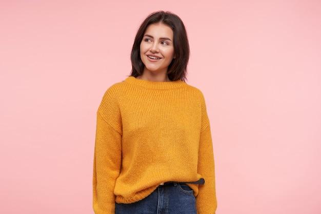 Allegra giovane donna dai capelli castani attraente con acconciatura casual sorridendo piacevolmente e tenendo le mani lungo il corpo mentre si sta in piedi sul muro rosa
