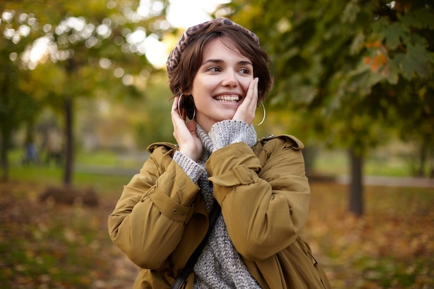 Cheerful young attractive brunette female with bob hairstyle keeping raised palm on her cheek and looking positively aside with charming smile, walking through city garden