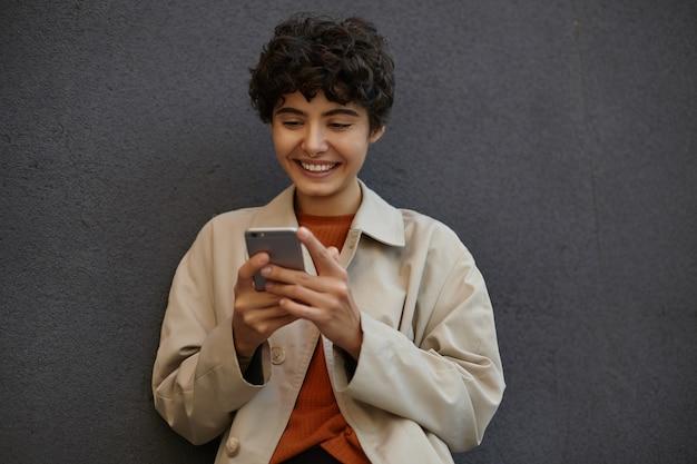 Веселая молодая привлекательная брюнетка с короткими вьющимися волосами стоит над черной городской стеной, болтает с друзьями по мобильному телефону и находится в приподнятом настроении, носит стильную одежду