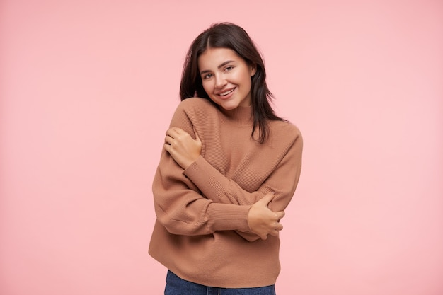 Giovane donna castana attraente allegra vestita in poloneck lavorato a maglia che si abbraccia e che guarda davanti con un sorriso piacevole, isolato sopra il muro rosa