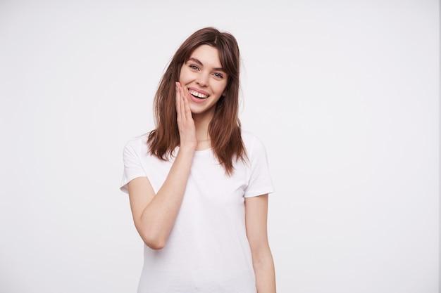 Веселая молодая привлекательная брюнетка женщина с повседневной прической, касаясь ее лица поднятой ладонью, позитивно глядя с широкой улыбкой, изолирована на белой стене