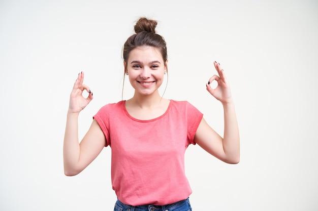 Giovane donna castana attraente allegra con trucco naturale che sorride volentieri alla macchina fotografica e che solleva le mani con il segno di namaste, isolato sopra fondo bianco