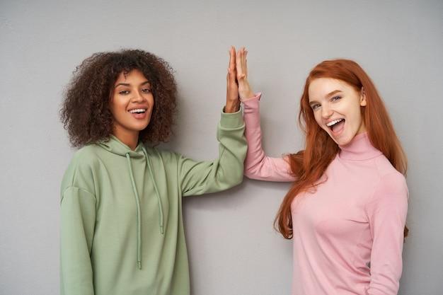 Allegre giovani donne attraenti alzando i palmi delle mani e dando cinque a vicenda guardando positivamente con ampi sorrisi, isolato su muro grigio
