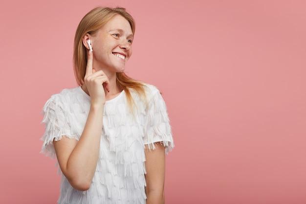 Allegra giovane donna attraente con i capelli volpi che inserisce l'auricolare nell'orecchio e guarda positivamente da parte con un ampio sorriso felice, vestita con una maglietta bianca elegante mentre si trova su sfondo rosa